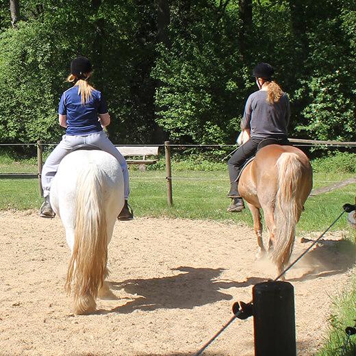 Zwei Mädchen reiten auf Ponys
